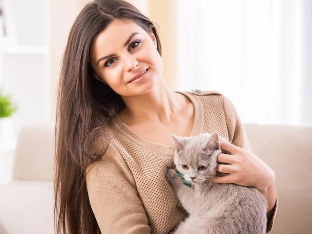 Ładna młoda kobieta z jej kotem na kanapie w domu.