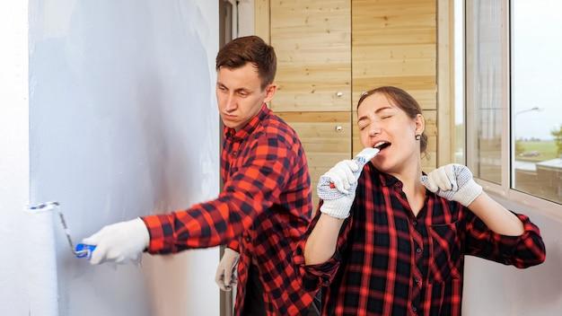 Ładna młoda kobieta z pędzlem śpiewa i tańczy, podczas gdy zmęczony mężczyzna maluje ścianę wałkiem naprawiając lekką przestronną przeszkloną loggię w domu