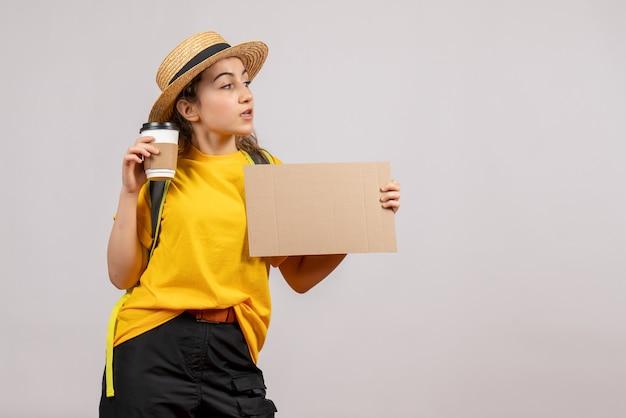 Ładna młoda kobieta z plecakiem trzymająca karton i kawę co