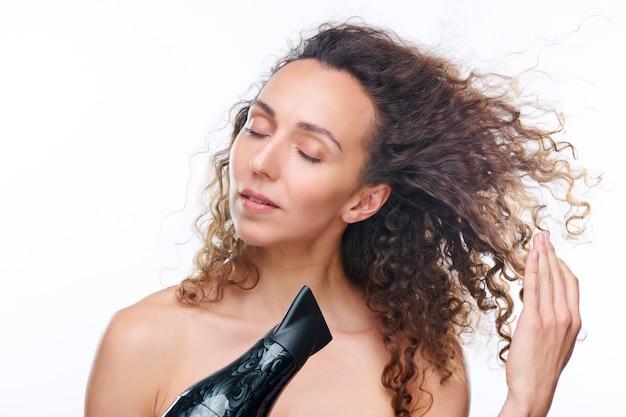 Ładna młoda kobieta z suszarką do włosów suszy swoje luksusowe brązowe, falowane czyste włosy po umyciu ich nowym rewitalizującym szamponem