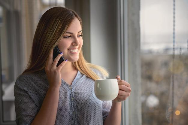 Ładna młoda kobieta z telefonem komórkowym przez okno. wysokiej jakości zdjęcie