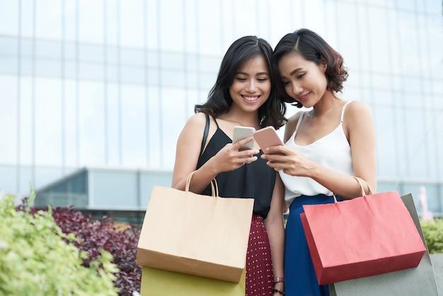 Ładna młoda kobieta z torbami na zakupy i smartfonami stojąca przed centrum handlowym i szukająca k...