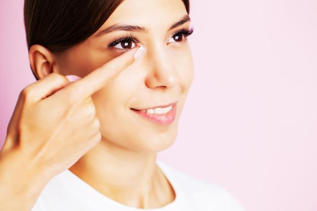 Ładna młoda kobieta zakłada soczewki kontaktowe dla wzroku