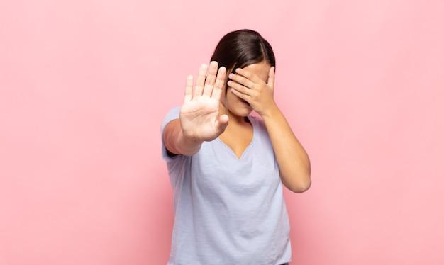 Ładna młoda kobieta zakrywająca twarz dłonią i wyciągająca drugą rękę do przodu, aby zatrzymać aparat, odmawiając zdjęć lub zdjęć