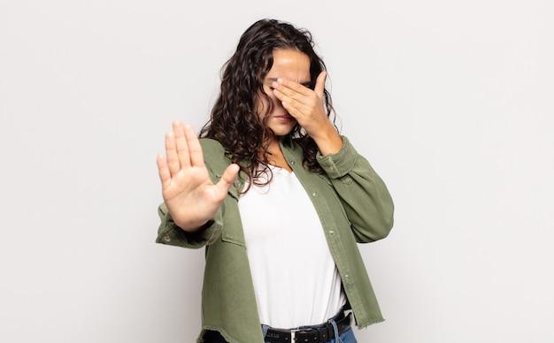 Ładna młoda kobieta zakrywająca twarz ręką i wyciągająca drugą rękę do przodu, aby zatrzymać przód, odmawiając zdjęć