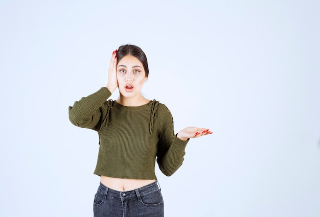 Ładna młoda kobieta zakrywająca ucho i pytająca, co się stało