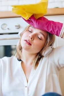 Ładna młoda kobieta zamykająca oczy i ocierająca pot z czoła