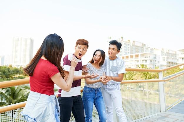 Ładna młoda kobieta zaskakuje swoich przyjaciół skupieniem, gdy stoją na moście
