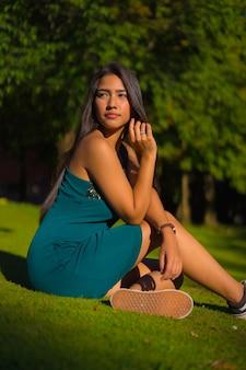 Ładna młoda latynoska brunetka z długimi prostymi włosami, ubrana w obcisłą zieloną sukienkę. portret dziewczynki siedzącej na trawie w parku z drzewami latem