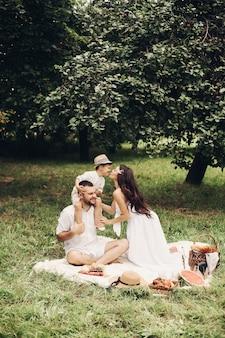 Ładna młoda mama całuje swoje dziecko w ogrodzie