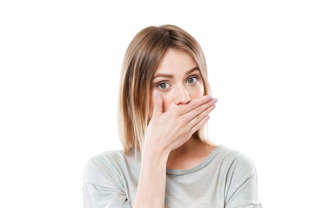 Ładna młoda młoda kobieta zakrywa jej usta ręką