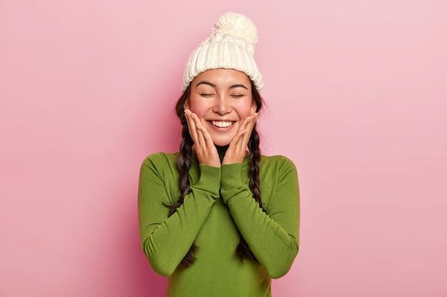 Ładna młoda modelka czuje przyjemność, dotyka policzków obiema dłońmi, nosi zimową ciepłą białą czapkę i swobodny zielony golf, ma szeroki, lśniący uśmiech, pozuje na różowej ścianie
