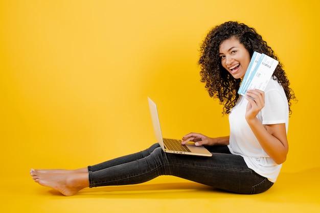 Ładna młoda murzynka siedzi z laptopem i samolotem biletami odizolowywającymi nad kolorem żółtym