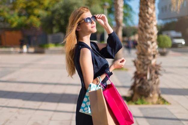 Ładna młoda nastolatek dziewczyna trzyma dużo torba na zakupy