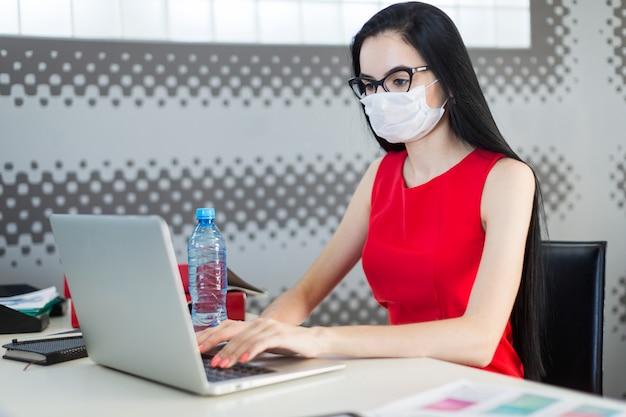 Ładna, młoda pani w czerwonej sukience, masce przeciwgazowej i okularach siedzi przy stole i pracuje