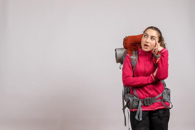 Ładna młoda podróżniczka z dużym plecakiem myśli o czymś stojącym na szaro