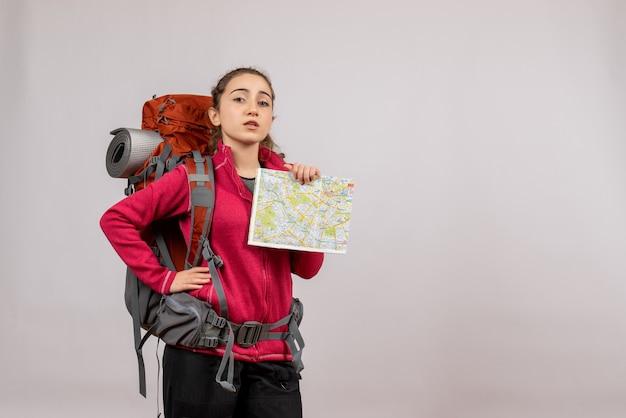 Ładna młoda podróżniczka z dużym plecakiem trzymająca mapę, kładąca dłoń w talii na szaro
