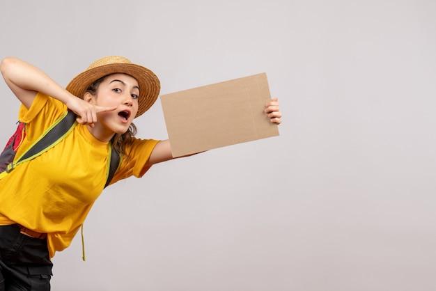 Ładna młoda podróżniczka z plecakiem trzymająca karton
