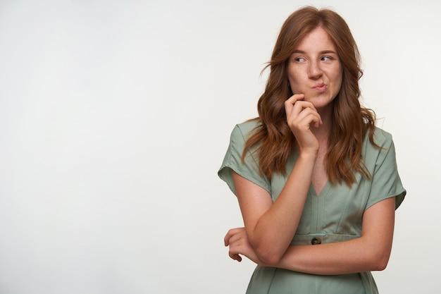 Ładna młoda rudowłosa kobieta trzymająca się za podbródek i gryząca policzek, wyglądająca na zaskoczoną, stojąca