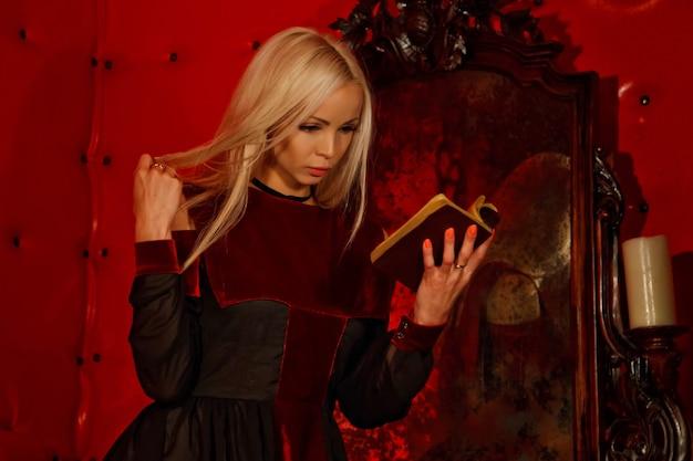Ładna młoda seksowna blondynka w gotyckiej sukience we wnętrzu średniowiecznego czerwonego pokoju ze starym lustrem czyta biblię i pokazuje emocje. obraz królowej horroru halloween. skopiuj miejsce na tekst lub logo
