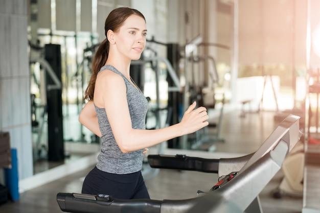 Ładna młoda sport kobieta biega na karuzeli w gym, zdrowy styl życia