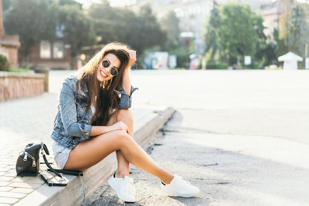 Ładna młoda uśmiechnięta brunetki dziewczyny relaksować plenerowy na ulicie.