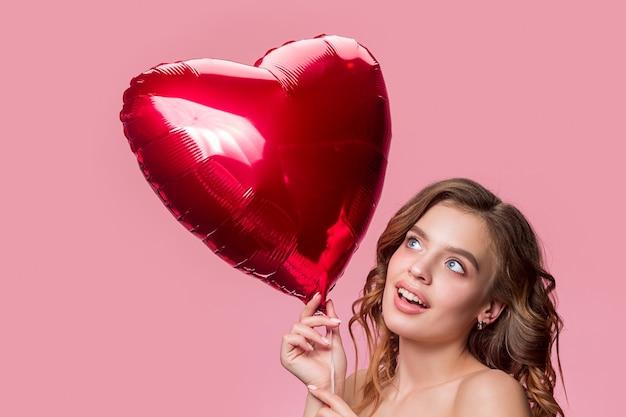 Ładna młoda uśmiechnięta kobieta z długimi falującymi jedwabistymi włosami, naturalny makijaż ręką w pobliżu podbródka na różowej ścianie. model o świeżej błyszczącej skórze i naturalnym makijażu. emocje ludzi
