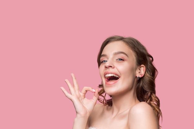 Ładna młoda uśmiechnięta kobieta z długimi falującymi jedwabistymi włosami, naturalny makijaż ręką w pobliżu podbródka na różowej ścianie.