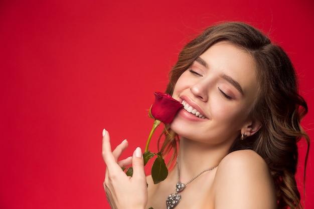 Ładna młoda uśmiechnięta kobieta z długimi falującymi jedwabistymi włosami, naturalny makijaż z czerwoną różą na tle czerwonej ściany. emocje ludzi. koncepcja walentynek