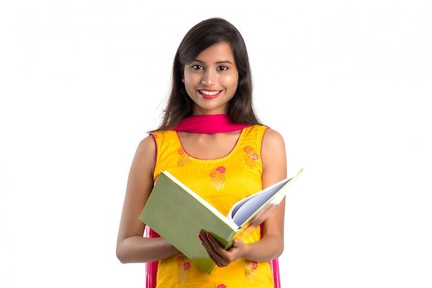 Ładna młodej kobiety mienia książka i pozować na bielu