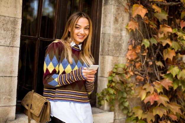 Ładna młodej kobiety pozycja z telefonem komórkowym na ulicie przy jesień dniem