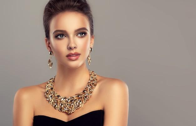 Ładna modelka prezentuje atrakcyjny makijaż i szykowną biżuterię z naszyjnikiem i kolczykami