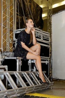 Ładna modelka siedząca wśród skrzyń na sprzęt na zapleczu