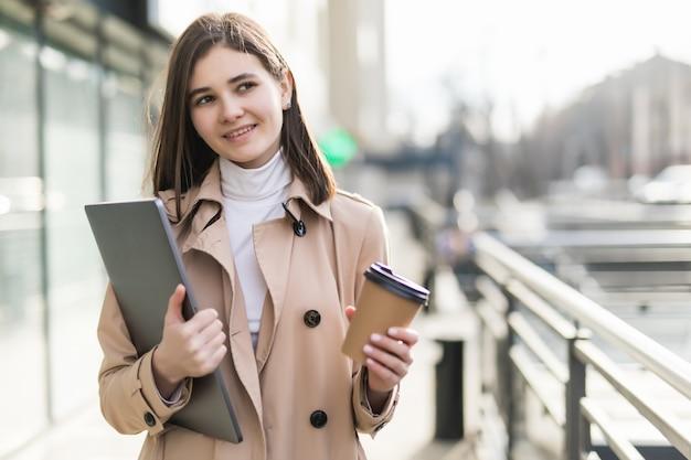 Ładna modelka w przypadkowych ubraniach zostaje z laptopem i kawą na zewnątrz