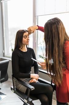 Ładna modelka w salonie piękności robi wieczorowy makijaż