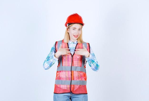 Ładna modelka wskazuje samą siebie, kładąc obie ręce blisko klatki piersiowej przed białą ścianą