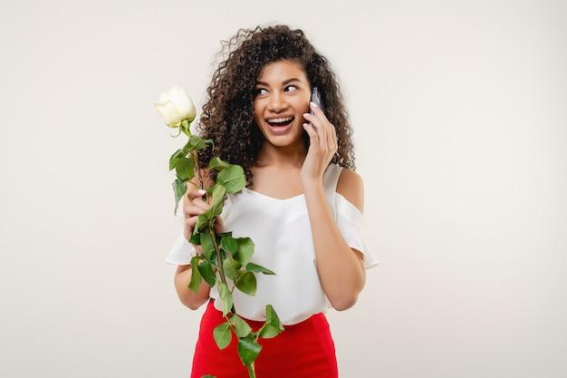 Ładna murzynka z różą opowiada na telefonie odizolowywającym