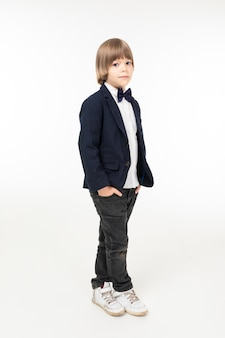 Ładna nastolatek chłopiec w czarnych kostiumów stojakach odizolowywających na białym tle