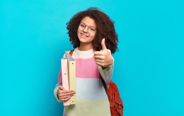 Ładna nastolatka afro czująca się dumna, beztroska, pewna siebie i szczęśliwa, uśmiechająca się pozytywnie z uniesionymi kciukami. koncepcja studenta