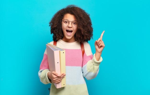 Ładna nastolatka afro czująca się jak szczęśliwy i podekscytowany geniusz po zrealizowaniu pomysłu, radośnie podnosząc palec, eureka !. koncepcja studenta