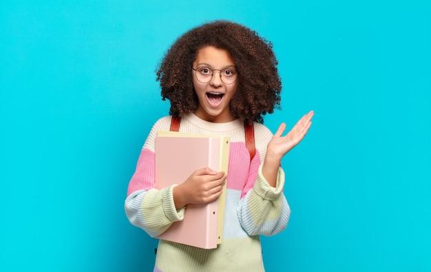 Ładna nastolatka afro czująca się szczęśliwa, podekscytowana, zaskoczona lub zszokowana, uśmiechnięta i zdumiona czymś niewiarygodnym. koncepcja studenta