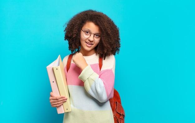 Ładna nastolatka afro czująca się szczęśliwa, pozytywna i odnosząca sukcesy, zmotywowana, gdy staje przed wyzwaniem lub świętuje dobre wyniki. koncepcja studenta