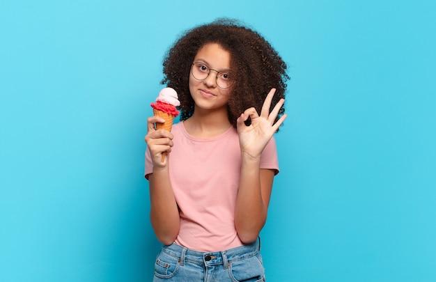 Ładna nastolatka afro czująca się szczęśliwa, zrelaksowana i usatysfakcjonowana, okazująca aprobatę dobrym gestem, uśmiechnięta. koncepcja lodów sumerskich