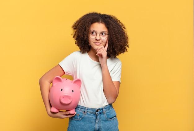 Ładna nastolatka afro czująca się zdziwiona i zdezorientowana, wątpiąca, ważąca lub wybierając różne opcje z zabawnym wyrazem twarzy. koncepcja oszczędności