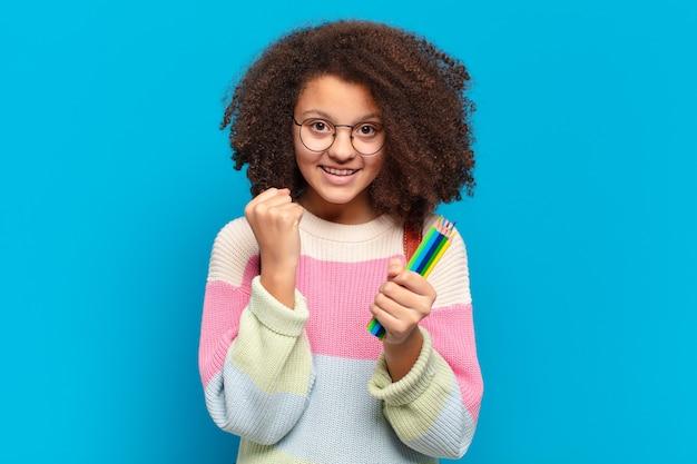 Ładna nastolatka afro czująca się zszokowana, podekscytowana i szczęśliwa, śmiejąca się i świętująca sukces, mówiąca wow !. koncepcja studenta