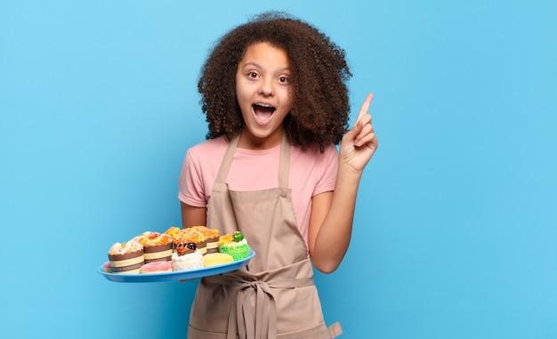 Ładna nastolatka afro czuje się jak szczęśliwy i podekscytowany geniusz po zrealizowaniu pomysłu