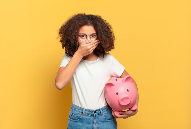Ładna nastolatka afro czuje się szczęśliwa, podekscytowana i zaskoczona, patrząc w bok z obiema rękami na twarzy. koncepcja oszczędności