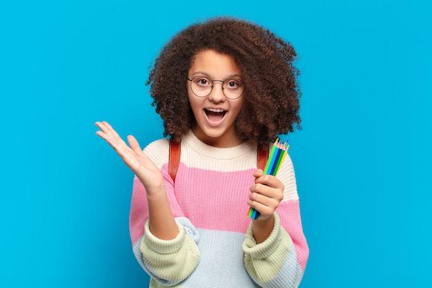 Ładna nastolatka afro czuje się szczęśliwa, podekscytowana, zaskoczona lub zszokowana, uśmiechnięta i zdumiona czymś niewiarygodnym. koncepcja studenta