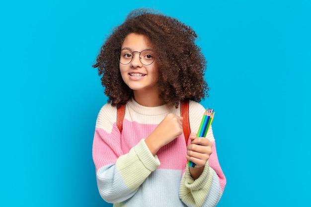 Ładna nastolatka afro czuje się szczęśliwa, pozytywna i odnosząca sukcesy, zmotywowana, gdy staje przed wyzwaniem lub świętuje dobre wyniki