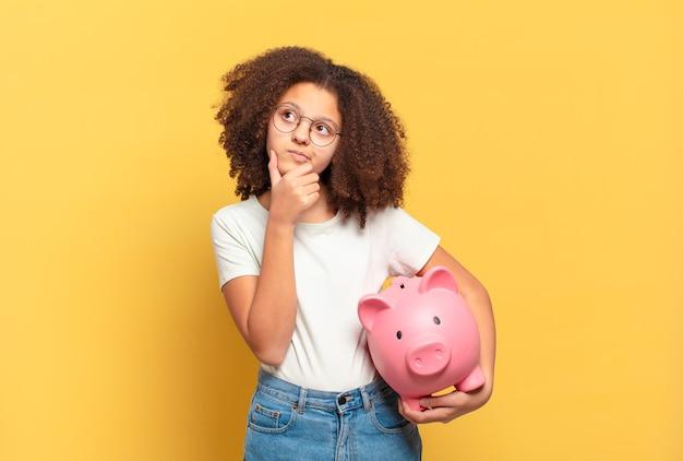Ładna nastolatka afro czuje się szczęśliwa, pozytywna i odnosząca sukcesy